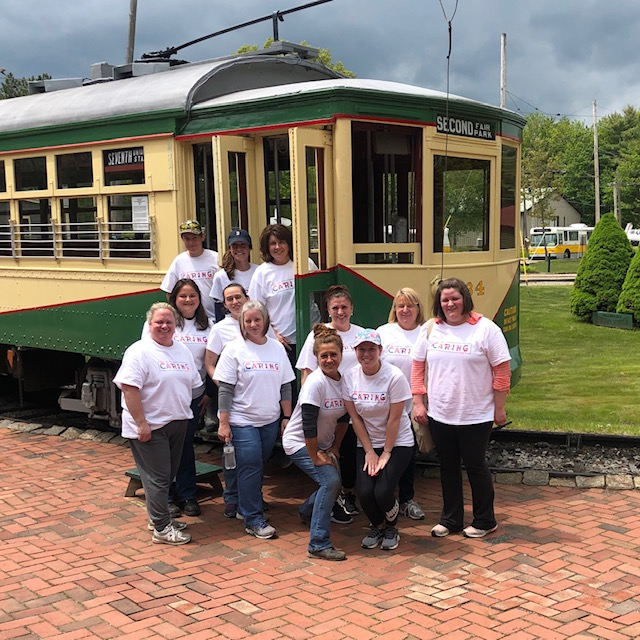 A group of Biddeford Savings volunteers poses for a photo in front of a trolley at the Seashore Trolley Museum in Kennebunkport