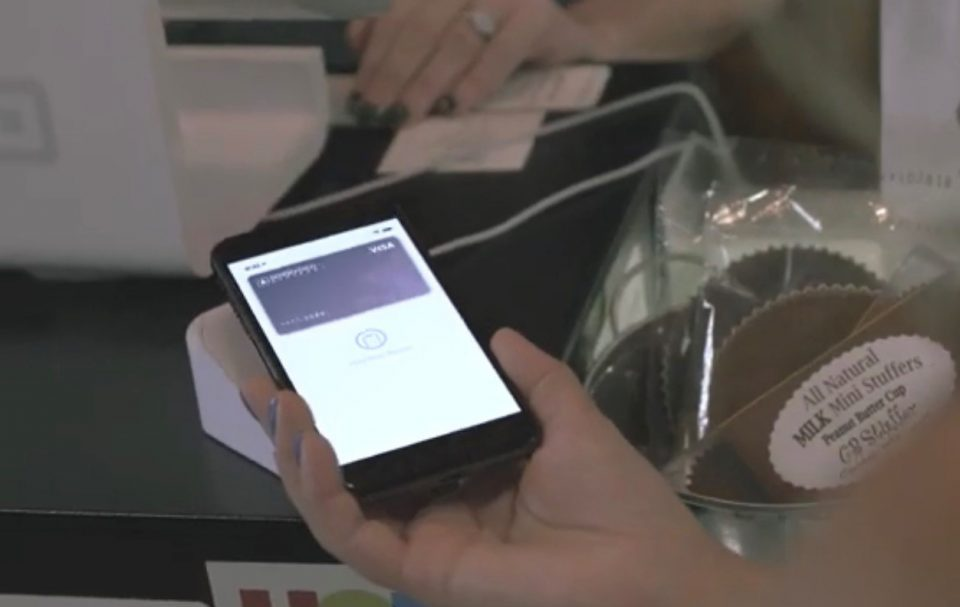 Person holding smartphone over contactless payment reader with image of Biddeford Savings debit card on the phone screen