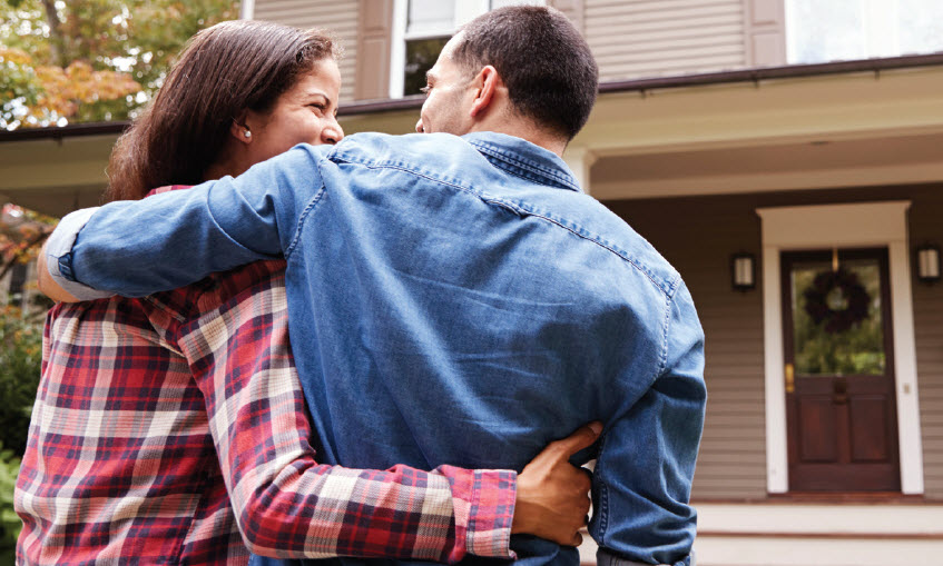New Homeowners in front of home