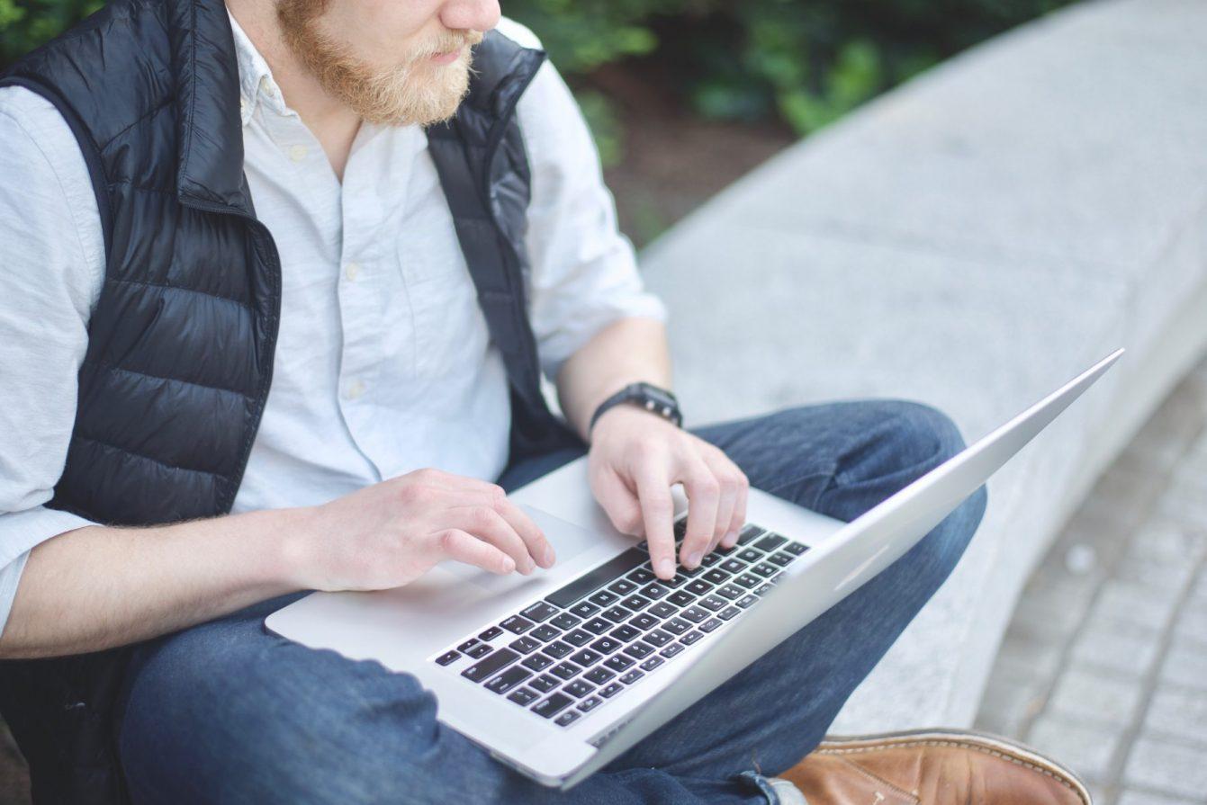 Man sitting on granite bench working on laptop